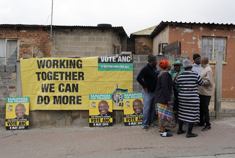 South Africans discussing election beside election posters